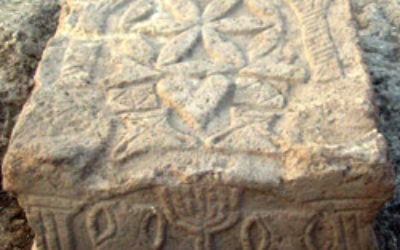 A stone engraved with a menorah from a Second Temple period synagogue was excavated at Migdal in Israel. Photo: Isranet