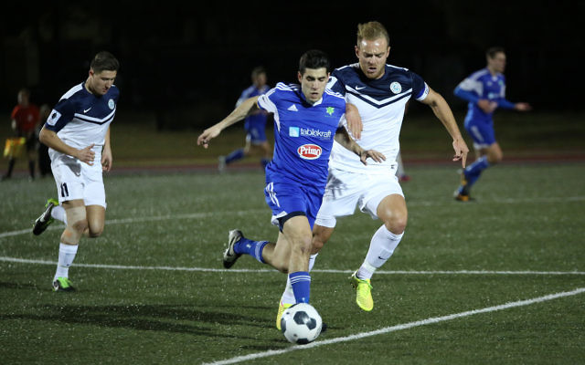 Hakoah's Jarrod Basger manoeuvres past Palm Beach captain Justyn McKay in their FFA Cup round of 32 clash. Photo: Noel Kessel