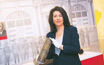 Curator Deborah Rechter holds a shell casing that was transformed into trench art during World War I. Photo: Peter Haskin
