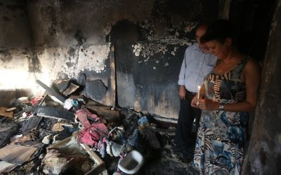 Israeli peace activists hold a candle in the Dawabsheh family's burnt-out home. Photo: AFP Photo/Jaafar Ashtiyeh