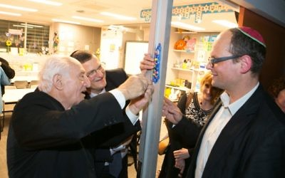 From left: Aron Kleinlehrer, Shmuel Ben-Shmuel, Tracey Waxman and Adam Carpenter, head of Jewish life (primary), affix a mezuzah made by students to the doorpost of a new classroom. Photo: Ofer Levy