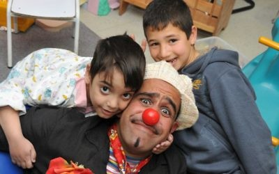 "David ""DuSH"" Barashi, Hadassah Hospital's head medical clown, with two young admirers."