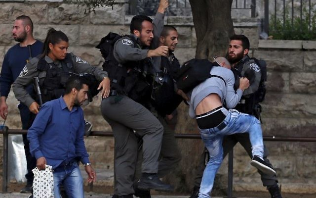 Border Police officers scuffle with a Palestinian protester as they detain him near Damascus Gate outside Jerusalem's Old City.