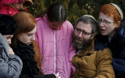 The husband and children of Dafna Meir mourn during her funeral ceremony in Otniel.