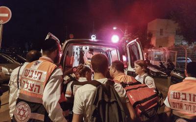 Megan Bernitz (right) helping a patient into an ambulance after last week's terrorist attack in Tel Aviv. Photo: Moti Karelitz/Flash90.