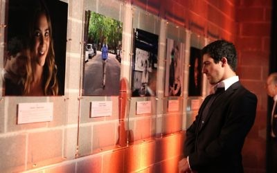 Cameron Graf examines photographs on display at the launch of the Humans of JCA exhibition. Photo: Giselle Haber