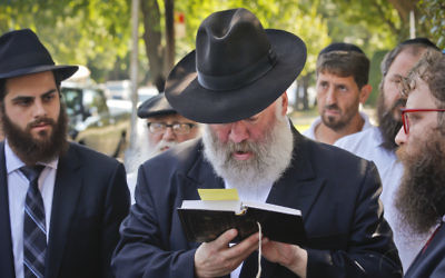 Norman Rosenbaum recites memorial prayers last week at the site where his brother Yankel Rosenbaum was stabbed during the 1991 Crown Heights riots. Photo: AP Photo/Bebeto Matthews.