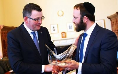 Premier Daniel Andrews (left) is presented with a shofar from Rabbi Rabin.