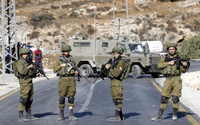Cap: Israeli soldiers near the scene of Saturday's attack in Hebron.  Photo: EPA/Abed Al Hashlamoun.