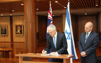 Prime Minister Malcolm Turnbull signs a condolence book in Canberra in honour of Shimon Peres. Pictured next to him is president of the Senate, Stephen Parry.