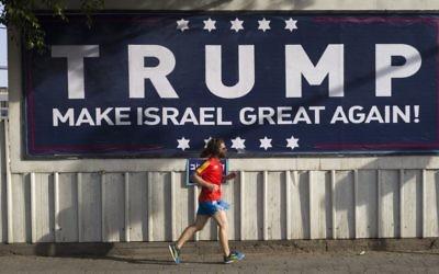 An Israeli jogger passes a pro-Trump placard in Tel Aviv. Photo: EPA/Jim Hollander