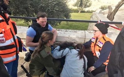 Dovi Meyer (back) helping to treat a victim of the January 8 terror attack in Jerusalem.