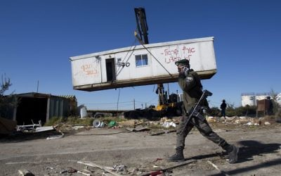 An Israeli border policeman walks near workers lifting a housing unit with a crane during the demolition of Amona on Tuesday. Photo: EPA/Abir Sultan