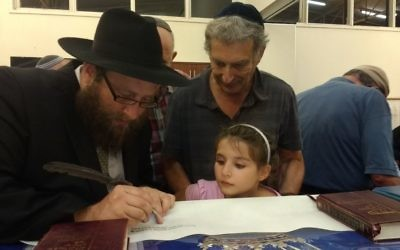 Rabbi Gutnick writing in the Torah with Tony and Maggie Hakin looking on.
