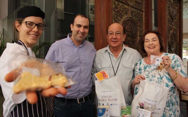 From left: Pastry chef Noa Nisell and her husband, JNF's education shaliach Yigal Nisell, present Purim mishloach manot packages to Mark Moran Vaucluse Seniors Living residents Bert and Dinah Danon on March 10.