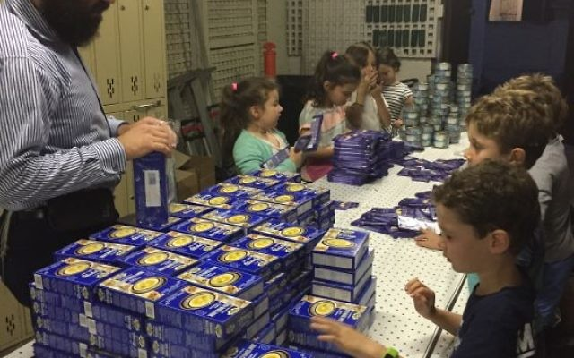 """Shlomo Nathanson packing Pesach hampers with C Care """"angels""""."""