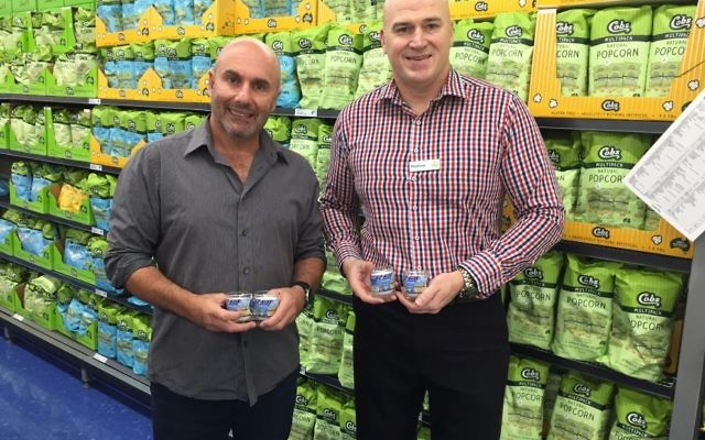 Danny Hochberg (left) and Woolworths Double Bay manager Matthew Walsh with memorial candles that will be in the Zachor Project reading kits.