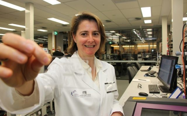 Dr Dorit Samocha-Bonet holding a micro-fluid chip inside the Garvan-Weizmann Centre for Cellular Genomics. Photo: Shane Desiatnik