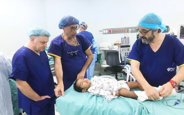 Australian medical personnel (from left) Michael Gordon, Rob Berkowitz and Mark Fajgman treat a young patient in Fiji.