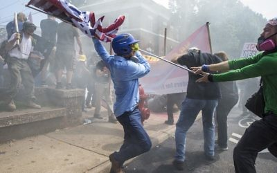 A white supremacist trying to strike a counterprotester with a white nationalist flag during clashes in Charlottesville. Photo: Samuel Corum/Anadolu Agency/Getty Images/JTA