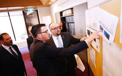 From left: Philip Dalidakis, Premier Daniel Andrews and Rabbi Gersh Lazarow study plans for the TBI upgrade during the Premier's tour of the synagogue. Photo: Peter Haskin