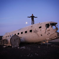 Dovi Broner is pictured on the wreckage of a US Navy plane in Iceland.