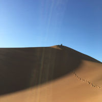 Jenny Lewin and daughter Jackie rest at the top of a sand dune in the Sahara Desert.