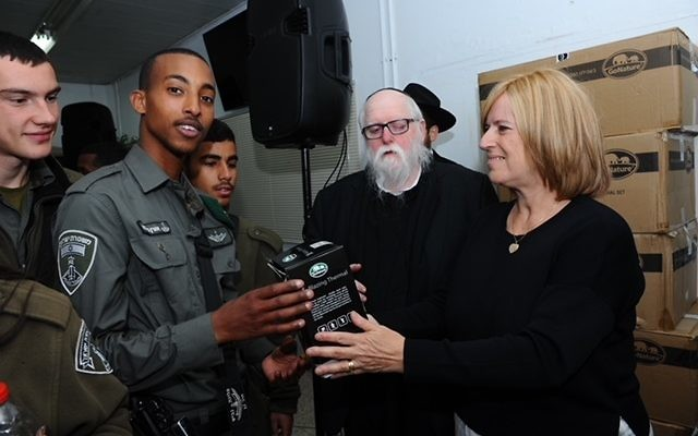 Saul Spigler (second from right) and his wife Beverly gifting thermal clothing to soldiers in Hebron.
