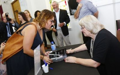 Author Heather Morris signs a copy of The Tattooist of Auschwitz at the book lunch at the Jewish Holocaust Centre in Melbourne in February. Photo: Peter Haskin