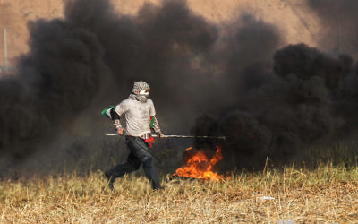 A Palestinian protester burning tyres during clashes with Israeli forces near the Gaza border. Photo: Said Khatib/AFP/Getty Images