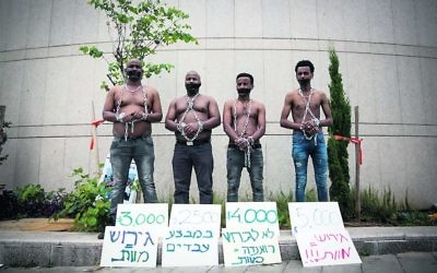African asylum seekers set up a mock slave auction as part of a protest outside the Ministry of Defence on Tuesday. Photo: Miriam Alster/Flash90