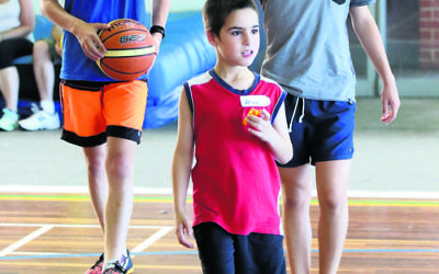 Alex joined other children from the Sydney Friendship Circle at a sports day with Maccabi junior basketball players in 2015. Photo: Noel Kessel