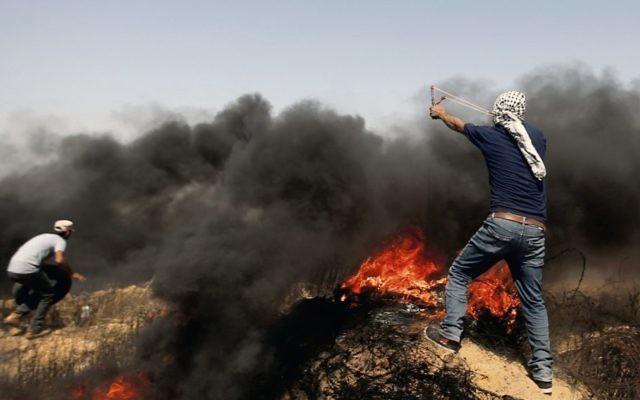 Palestinians hurl stones and burning tires near the Gaza border earlier this month. Photo: AP Photo/Adel Hana