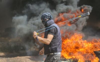 A Palestinian protester uses a sling to hurl stones towards Israeli forces during clashes along the Gaza border. Photo: AAP Image/CrowdSpark/Mhmed Ali