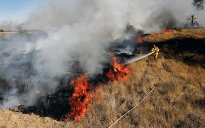 Israeli firefighters try to douse a fire near Kibbutz Or Haner caused by kites from Gaza carrying Molotov cocktails. Photo: EPA/Abir Sultan