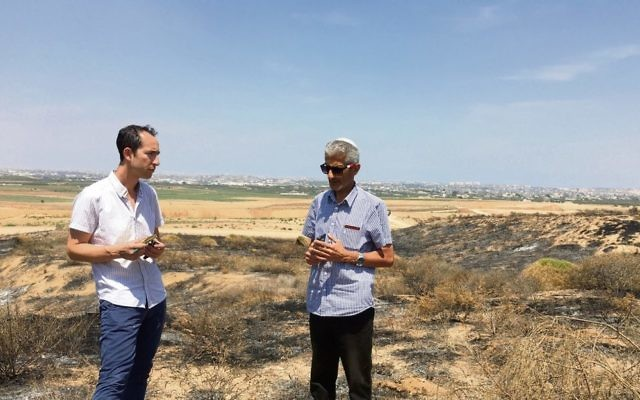The AJN's Nathan Jeffay (left) with Eyal Hagbi on a patch of land scorched by a kite fire.