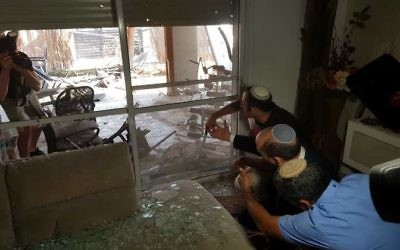 Sderot residents survey the damage to a house caused by a rocket from Gaza. Photo: Sderot Municipality