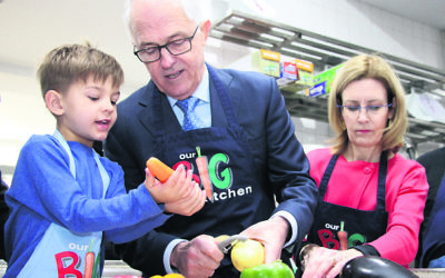 Look, this is how you do it! Jack at Our Big Kitchen with his grandfather, Prime Minister Malcolm Turnbull, and Vaucluse MP Gabrielle Upton. Photo: Shane Desiatnik