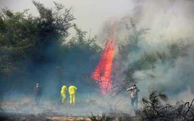 Israeli firefighters trying to extinguish a fire at the Carmia nature reserve last month, believed to have been ignited by a fire kite or balloon from Gaza. Photo: EPA/Abir Sultan