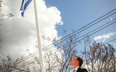 Dvir Abramovich raises Israel's flag at St Kilda Town Hall. Photo: Sav Schulman