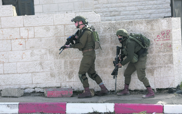 Israeli soldiers conduct a search in Ramallah  for suspects behind the shooting attack. Photo: AP Photo/Majdi Mohammed