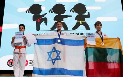 Gold medallist Sela Elmaliah holding the Israeli flag. Photo: Shachar Hoshmand