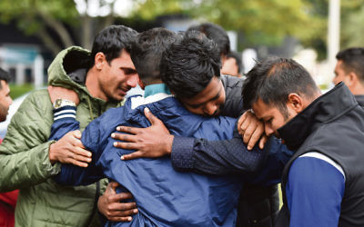 Friends of a missing man grieve outside a refuge centre in Christchurch last Sunday. Photo: AAP Image/Mick Tsikas