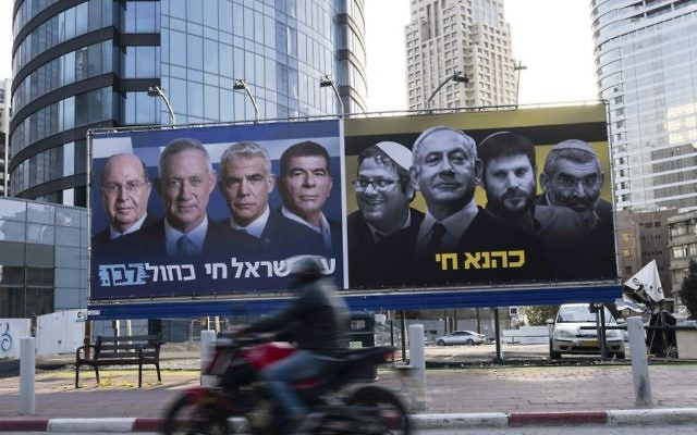"""An Israeli motorcyclist passes billboards put up by the Blue and White alliance featuring their candidate for prime minister, Benny Gantz, alongside his fellow party leaders next to a panel showing Benjamin Netanyahu and extreme right-wing politicians. On the right side the Hebrew translates as """"Kahane lives"""" and on the left reads, """"People of Israel live Blue and White"""". Photo: EPA/Jim Hollander"""