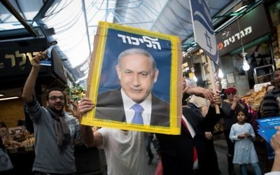 A Likud party supporter holds a picture of Israeli Prime Minister Benjamin Netanyahu at the Mahane Yehuda market in Jerusalem, April 7, 2019. (Yonatan Sindel/Flash90)