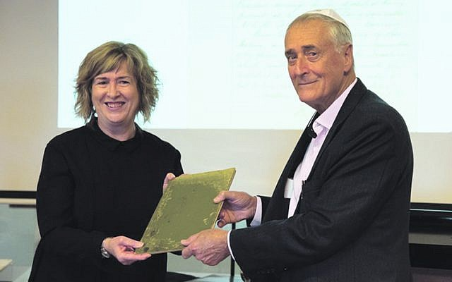 Queensland State Librarian Vicki McDonald accepts a building committee minute book of the Brisbane Hebrew Congregation from Dr Michael Briner.