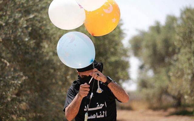 A Palestinian youth in Gaza prepares Molotov cocktails attached to balloons to set fire to Israeli land, May 31, 2019. (Hassan Jedi/Flash90)