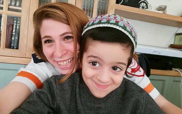 Yotam Cohen, 7, with MDA paramedic Yonat Daskal-Dagan.
