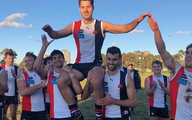 Jeremy Forbes celebrates his 100th match with teammates last Saturday