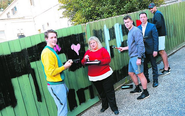 From left: Riley Collier-Dawkins, Aliza Shuvaly, Maverick Weller, Dvir Abramovich and Toby Nankervis cover antisemitic graffiti on a fence at Aliza's Place Cafe in Chadstone. Photo: Peter Haskin